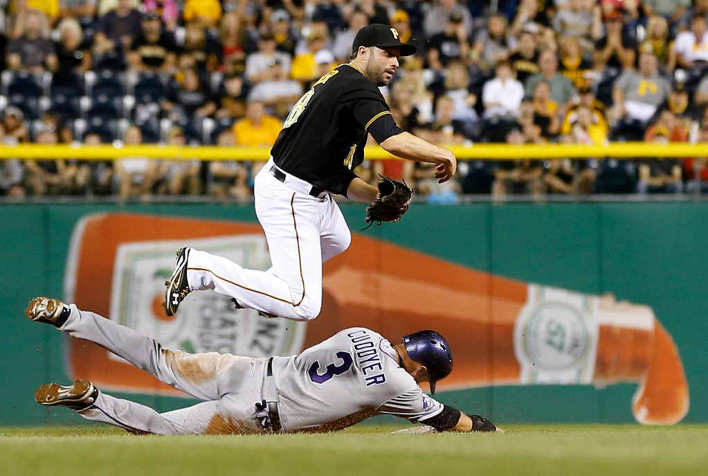. Pittsburgh Pirates second baseman Neil Walker hops over Colorado Rockies\' Michael Cuddyer at second as he competes the throw to first for a double play on Wilin Rosario in the eight inning of the baseball game on Saturday, Aug. 3, 2013, in Pittsburgh. (AP Photo/Keith Srakocic)