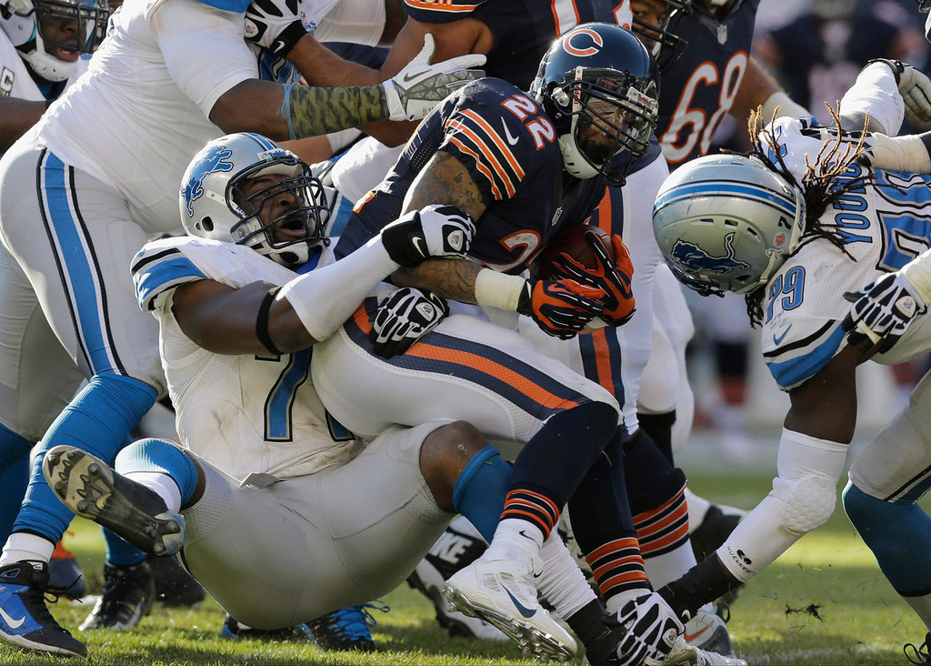 . Chicago Bears running back Matt Forte (22) is tackled by Detroit Lions defensive end Israel Idonije during the second half of an NFL football game, Sunday, Nov. 10, 2013, in Chicago. (AP Photo/Nam Y. Huh)
