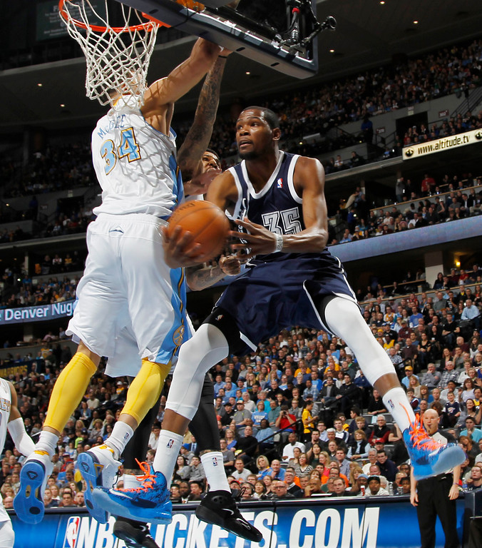 . Oklahoma City Thunder forward Kevin Durant, right, goes up for a reverse layup past Denver Nuggets forward JaVale MGee in the first quarter of an NBA basketball game in Denver on Friday, March 1, 2013. (AP Photo/David Zalubowski)