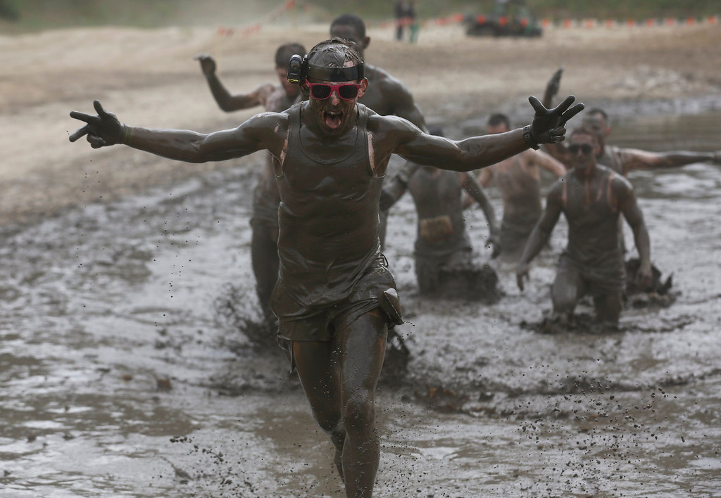 """. A participant of the \""""Tough Mudder\"""" endurance event series runs through the \""""mud-mile obstacle\"""" in the Fursten Forest, a former British Army training ground near the north-western German city of Osnabrueck July 13, 2013. The hardcore but un-timed event over 16 km (10 miles) was designed by British Special Forces to test mental as well as physical strength. Some 4,000 competitors had to overcome obstacles of common human fears, such as fire, water, and heights.   REUTERS/Wolfgang Rattay"""