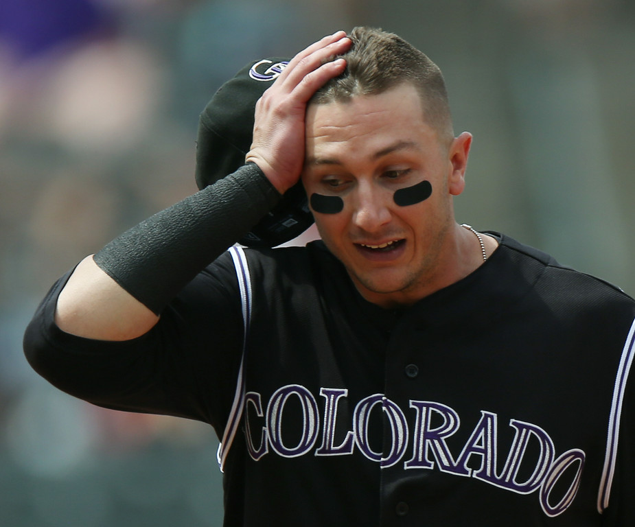 . Colorado Rockies shortstop Troy Tulowitzki reacts after Minnesota Twins starting pitcher Kevin Correia doubled in a run in the fourth inning of an interleague baseball game in Denver on Saturday, July 12, 2014. (AP Photo/David Zalubowski)