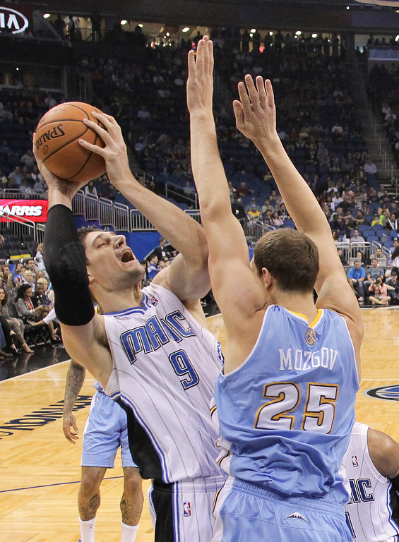 . Orlando Magic\'s Nikola Vucevic (9) makes a shot over Denver Nuggets\'s Timofey Mozgov (25) during the first half of an NBA basketball game in Orlando, Fla., Wednesday, March 12, 2014. (AP Photo/John Raoux)