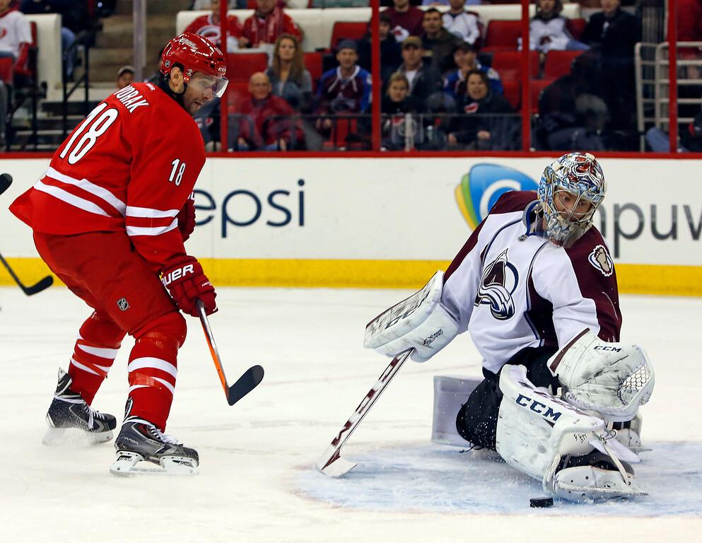 . Carolina Hurricanes\' Radek Dvorak (18), of the Czech Republic, has his shot blocked by Colorado Avalanche goalie Semyon Varlamov (1), of Russia, during the second period of an NHL hockey game in Raleigh, N.C., Tuesday, Nov. 12, 2013. (AP Photo/Karl B DeBlaker)