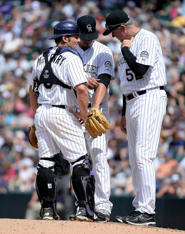 . Colorado Rockies starting pitcher Jhoulys Chacin (45) gets a visit from Colorado Rockies catcher Michael McKenry (8) and Colorado Rockies pitching coach Jim Wright (52) during the third inning May 4, 2014 at Coors Field. (Photo by John Leyba/The Denver Post)
