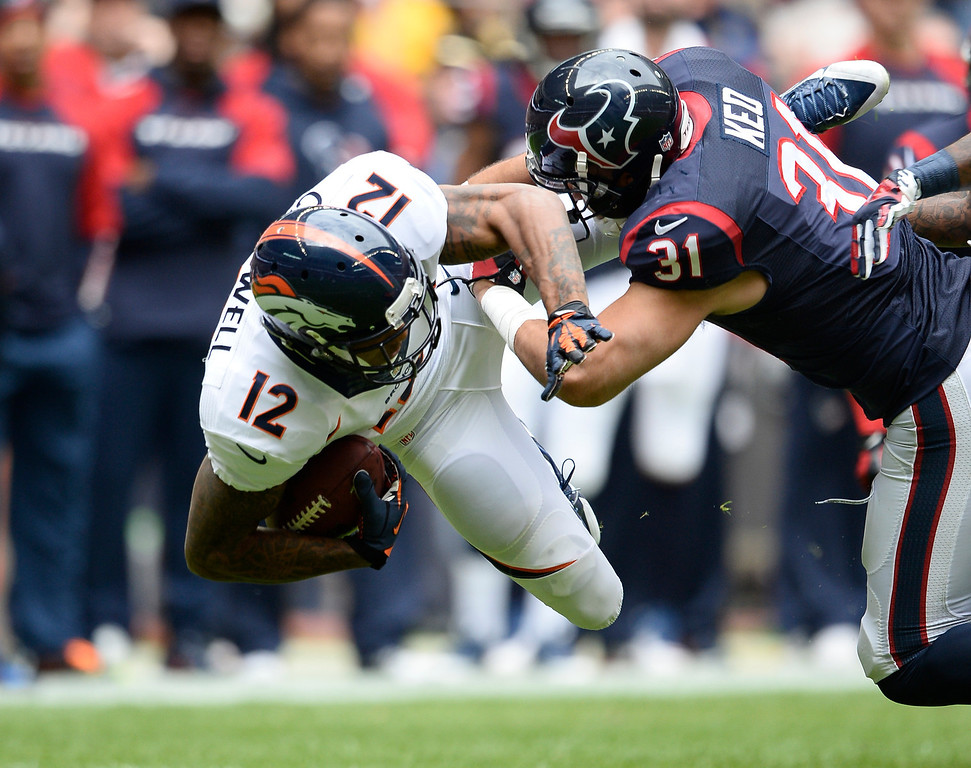 . HOUSTON, TX - DECEMBER 22: Denver Broncos wide receiver Andre Caldwell (12) gets upended by Houston Texans free safety Shiloh Keo (31) during the first quarter December 22, 2013 at Reliant Stadium. (Photo by John Leyba/The Denver Post)
