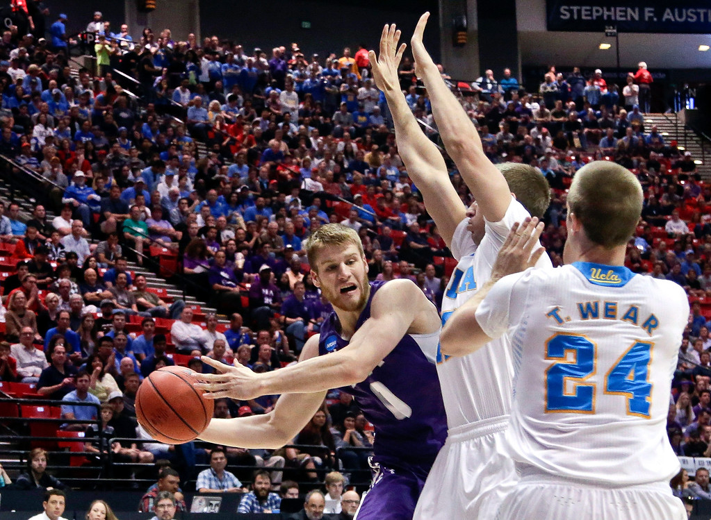 . Stephen F. Austin forward Nikola Gajic tries to make a wrap around pass against the defense of UCLA forwards David Wear and Travis Wear in a third-round game in the NCAA college basketball tournament, Sunday, March 23, 2014, in San Diego. (AP Photo/Gregory Bull)