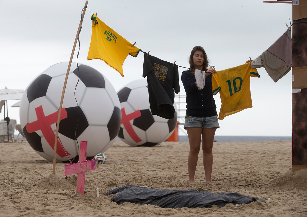 . An activist from Rio da Paz Brazil performs as she hangs soccer jerseys on a clothesline next to a tent to symbolize a slum, next to a fake tombstone and large inflatable soccer balls covered with red crosses, on Copacabana beach to protest government spending on the World Cup in Rio de Janeiro, Brazil,Tuesday, June 10, 2014. Brazil has seen near-daily protests with anger focused on the billions spent to host the international soccer tournament. (AP Photo/Silvia Izquierdo)