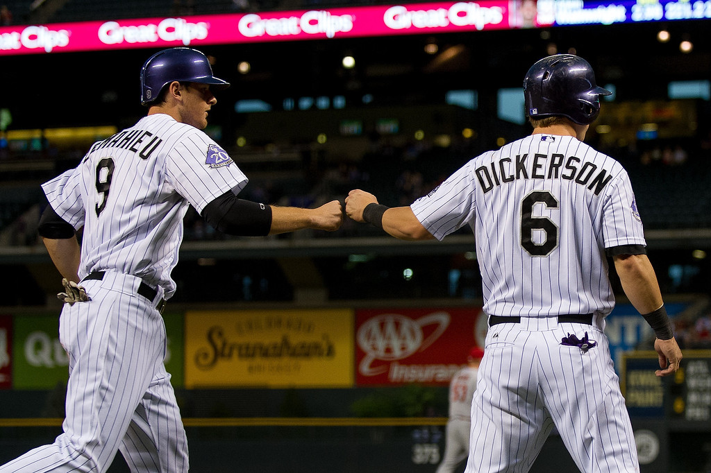 . DJ LeMahieu #9 and Corey Dickerson #6 of the Colorado Rockies celebrate a pair of first inning runs on a single by Troy Tulowitzki #2 (not pictured) against the St. Louis Cardinals at Coors Field on September 18, 2013 in Denver, Colorado. (Photo by Dustin Bradford/Getty Images)