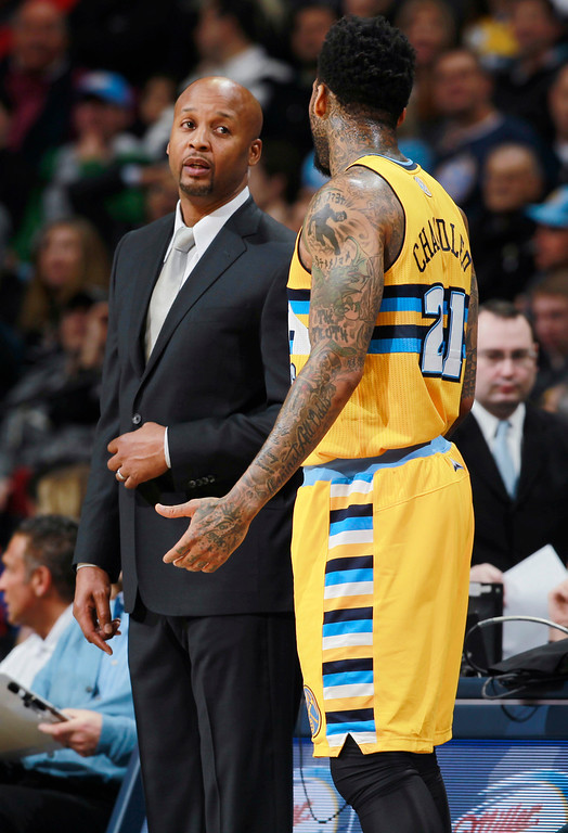 . Denver Nuggets head coach Brian Shaw, back, talks with forward Wilson Chandler as he prepares to put the ball back into play against the Phoenix Suns in the first quarter of an NBA basketball game in Denver on Friday, Dec. 20, 2013. (AP Photo/David Zalubowski)