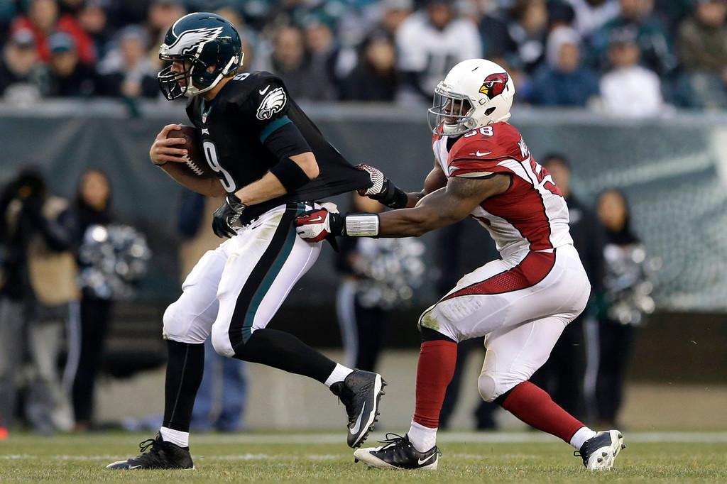 . Philadelphia Eagles\' Nick Foles, left, is tackled by Arizona Cardinals\' Daryl Washington during the second half of an NFL football game on Sunday, Dec. 1, 2013, in Philadelphia. (AP Photo/Matt Rourke)