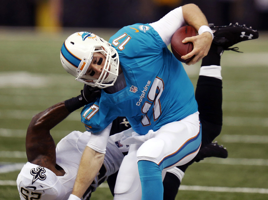 . Miami Dolphins quarterback Ryan Tannehill (17) is dragged down by New Orleans Saints defensive back Rafael Bush (25) in the first half of an NFL football game in New Orleans, Monday, Sept. 30, 2013. (AP Photo/Bill Haber)