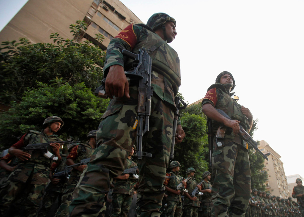". Army soldiers stand guard in front of protesters who are against Egyptian President Mohamed Mursi, near the presidential palace in Cairo July 3, 2013. The Egyptian president\'s national security adviser said on Wednesday that a ""military coup\"" was under way and army and police violence was expected to remove pro-Mursi demonstrators. REUTERS/Amr Abdallah Dalsh"