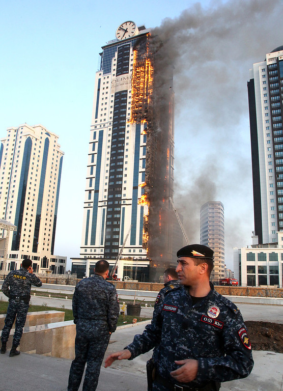 . Chechen policemen put cordons round a burning building in central Grozny on April 3, 2013. A fire raged in a skyscraper in the Chechnya capital Grozny on Wednesday, a building which is a centrepiece of a drive by local authorities to promote the city as a glitzy and modern hub. The buildng is uninhabited.  ELENA FITKULINA/AFP/Getty Images