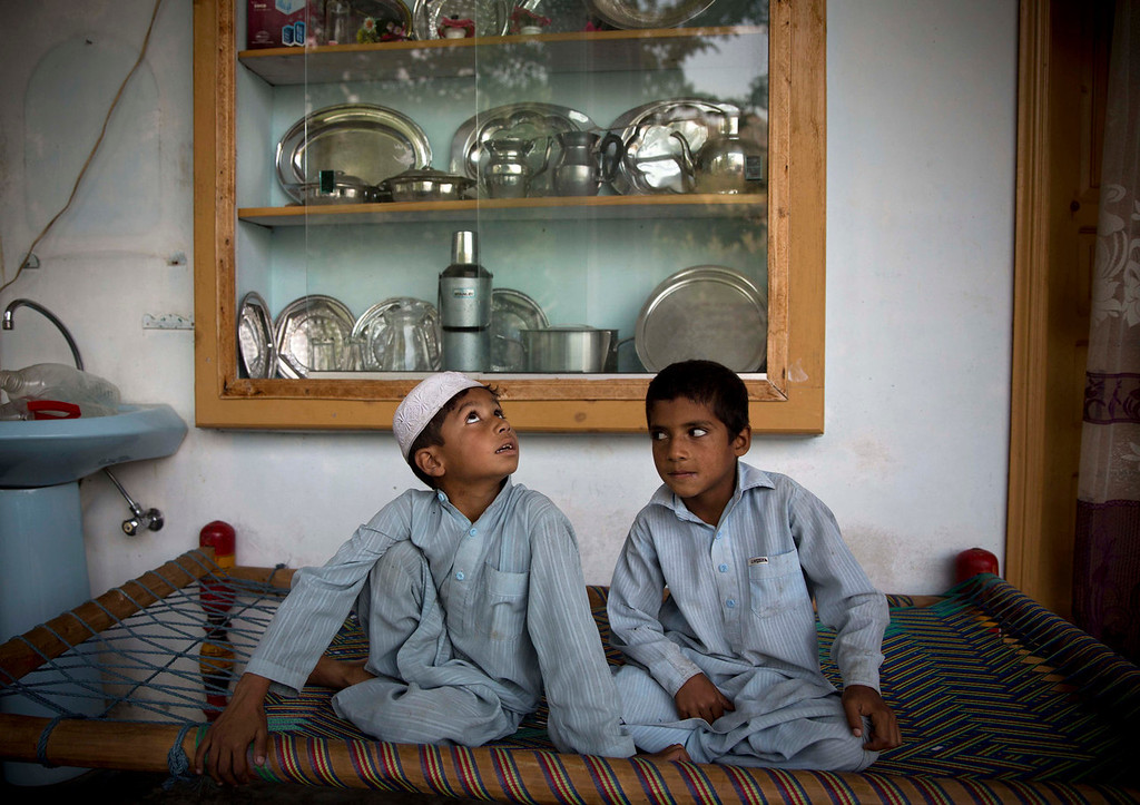 ". Haroon, 5, left, and Abdul Hamid, 8, neighbors of the man who is accused of shooting Malala Yousufzai a year ago, sit in his home in Ghawari Mastas, Swat Valley, Pakistan on Thursday, Oct. 3, 2013. Military officials say Malala\'s assailant Attaullah, has fled to Afghanistan, while the police say the case is closed. In a rare interview, Attaullah\'s sister told The Associated Press: ""We don\'t know where he is, whether he is dead or alive.\"" (AP Photo/Anja Niedringhaus)"