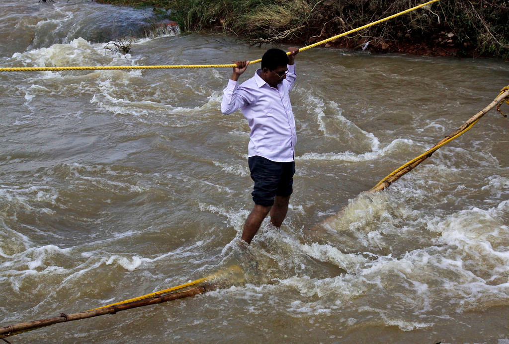 . An Indian villager negotiates his way through floodwaters with the help of ropes in Agastinuagaon, Ganjam district of Orissa state, India, Saturday, Oct. 26, 2013. As of Saturday, 39 people had died in flood-related incidents in Andhra Pradesh and Orissa states since the rains began Monday, according to officials quoted by the Press Trust of India. (AP Photo/Biswaranjan Rout)