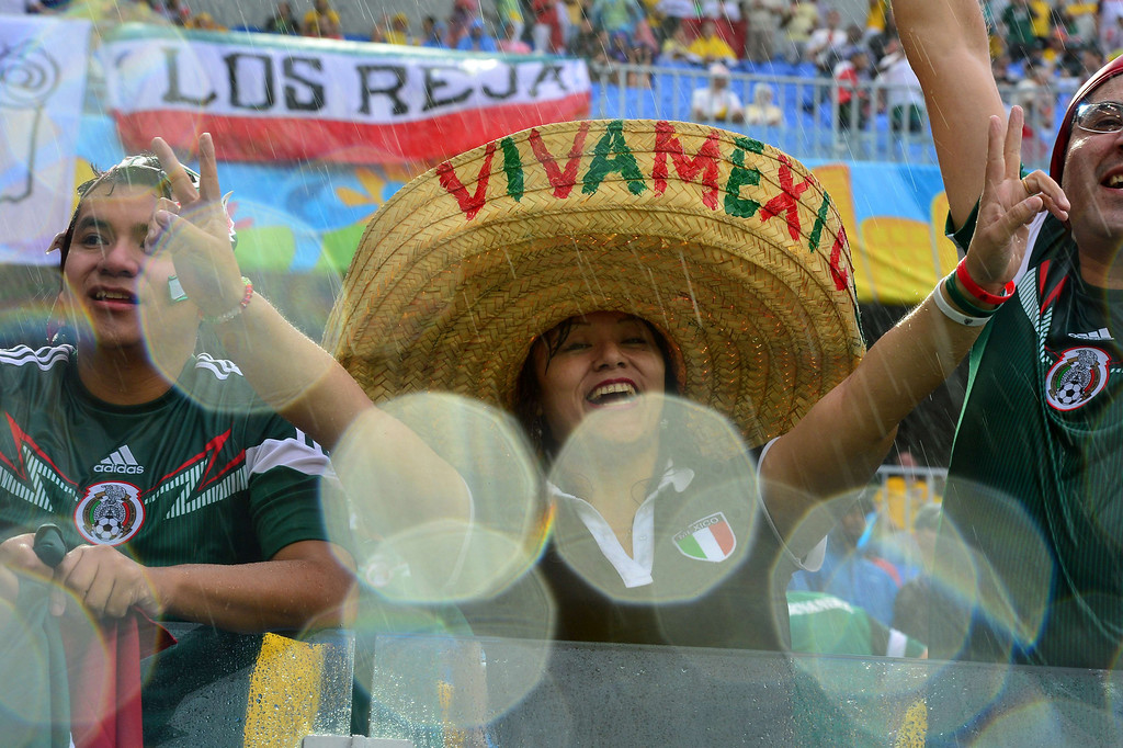 . Mexican football fans cheer for their team during the Group A football match between Mexico and Cameroon at the Dunas Arena in Natal during the 2014 FIFA World Cup on June 13, 2014.  YURI CORTEZ/AFP/Getty Images