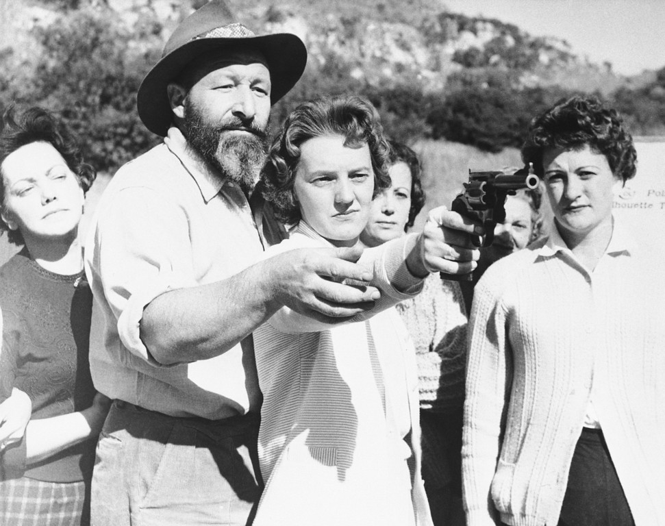 . Manny Laxton, a Johannesburg gunsmith, shows Delysia Scott, a Johannesburg housewife, how to handle a revolver at shooting range near Johannesburg, May 14, 1961. Many white women in South Africa are learning how to use firearms for self-protection in the event of racial unrest at the end of this month when South Africa becomes a republic outside the British Commonwealth. (AP Photo/Dennis Lee Royle)