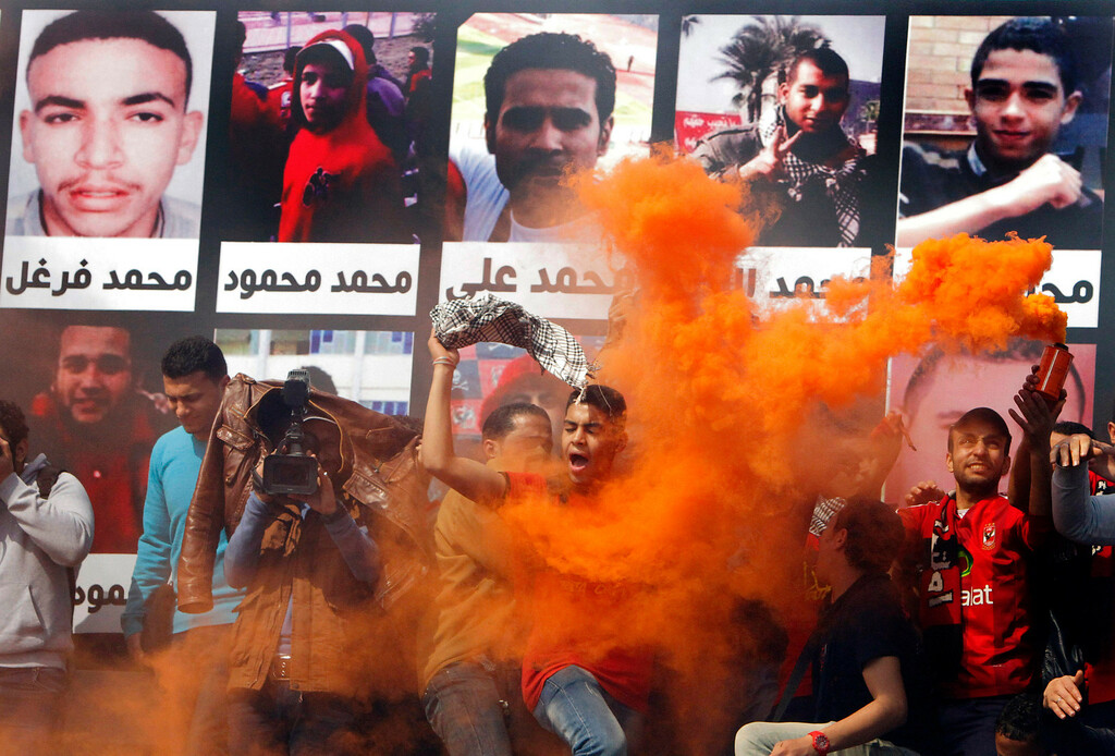 . An Egyptian soccer fan of Al-Ahly club shouts slogans in front of a banner at showing some pictures of the victims of a 2012 soccer riot, in the club headquarters in Cairo, Egypt, Saturday, March 9, 2013. An Egyptian court on Saturday confirmed the death sentences against 21 people for taking part in a deadly soccer riot but acquitted seven police officials for their alleged role in the violence. Suspected fans enraged by the verdict torched the soccer federation headquarters and a police club in Cairo in protest.(AP Photo/Amr Nabil)