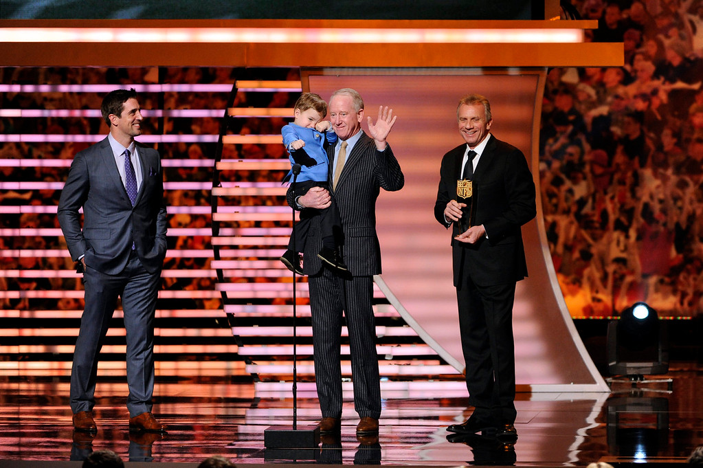. Aaron Rodgers of the Green Bay Packers, left, and former NFL quarterback Joe Montana, right, present the award for AP Most Valuable Player to Archie Manning, who accepted for his son Peyton Manning, at the third annual NFL Honors at Radio City Music Hall on Saturday, Feb. 1, 2014, in New York. Archie Manning holds his grandson Marshall Manning. (Photo by Evan Agostini/Invision for NFL/AP Images)