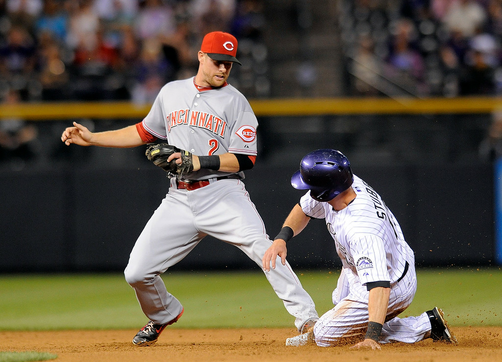 . Cincinnati Reds shortstop Zack Cozart forces out Colorado Rockies Drew Stubbs at second base in the fourth inning of a baseball game on Thursday, Aug. 14, 2014, in Denver. (AP Photo/Chris Schneider)