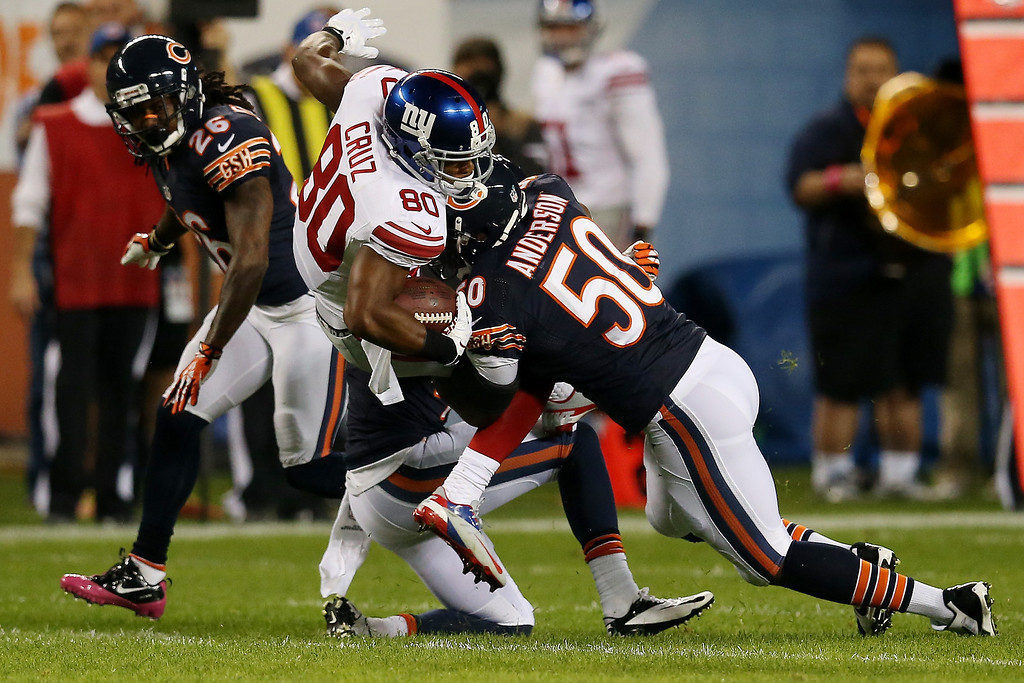 . Wide receiver Victor Cruz #80 of the New York Giants is tackled by outside linebacker James Anderson #50 of the Chicago Bears after making a catch in the first quarter during a game at Soldier Field on October 10, 2013 in Chicago, Illinois.  (Photo by Jonathan Daniel/Getty Images)
