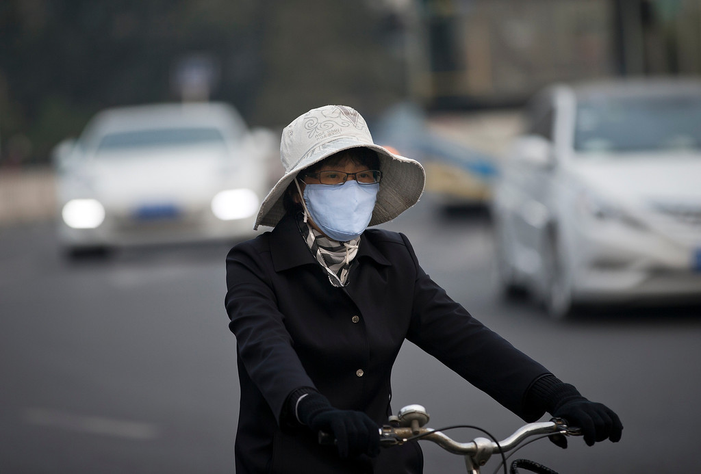 . A woman wearing a face mask bicycles on a road in Beijing Tuesday, Oct. 22, 2013. Beijing is seeking to tame its smog emergencies by preparing emergency measures such as factory shutdowns and traffic limits to kick in when air pollution levels are high. (AP Photo/Andy Wong)