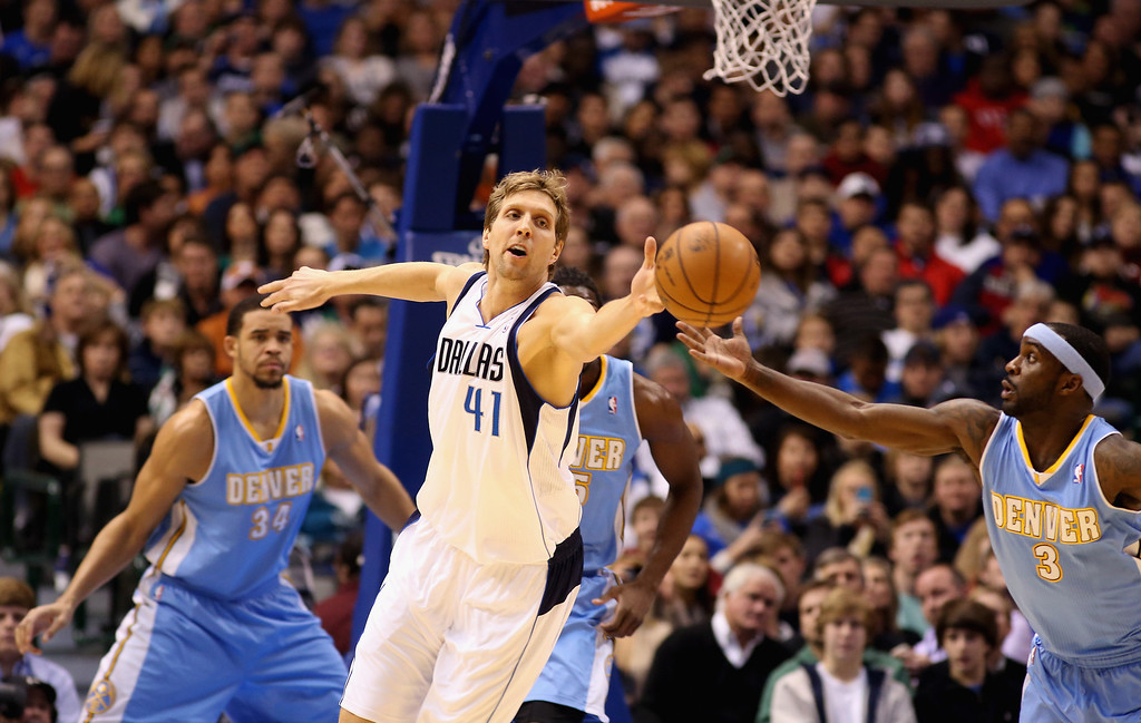 . Dirk Nowitzki #41 of the Dallas Mavericks reaches for a rebound against Ty Lawson #3 of the Denver Nuggets at American Airlines Center on December 28, 2012 in Dallas, Texas.      (Photo by Ronald Martinez/Getty Images)