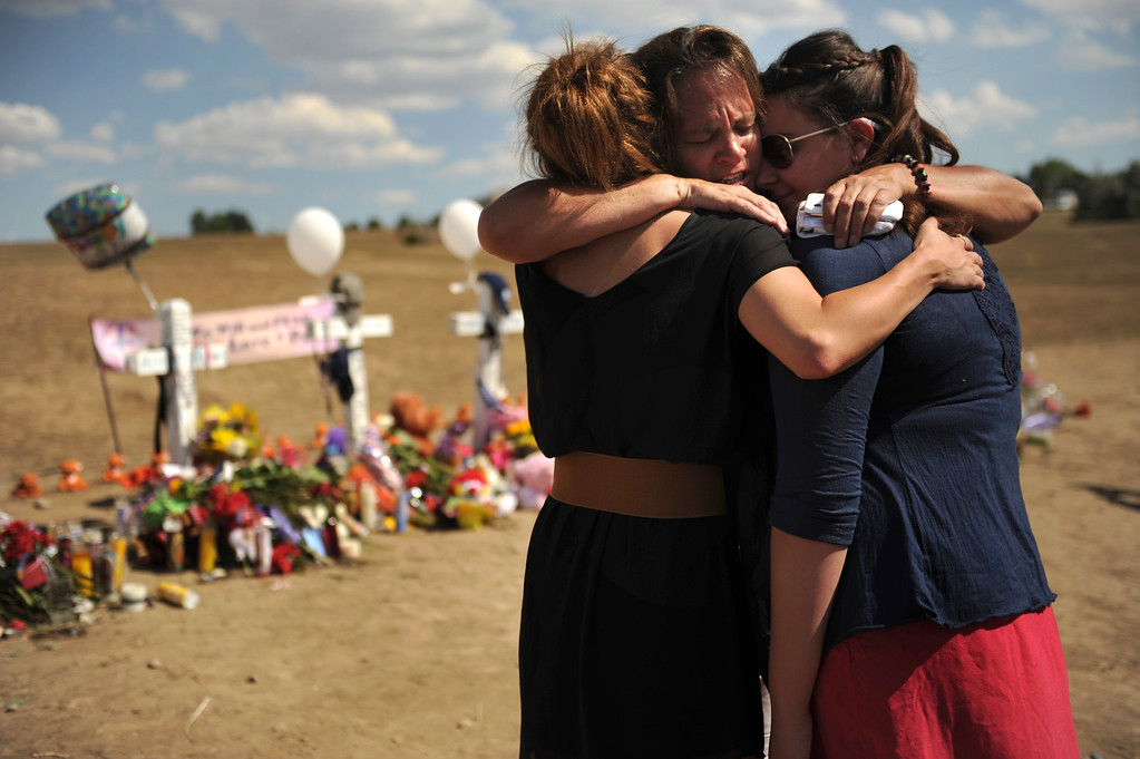 . Aubrey Podschwait 19 of Parker, Julia Kouris 51 of Denver and Olivia Mancuso 20 of Parker share a healing hug while visiting the memorial for the victims of the Century 16 Theater shooting  at the corner of Sable Boulevard and Centerpoint Drive in Aurora, Colorado Monday,  July 23,  2012.      Joe Amon, The Denver Post