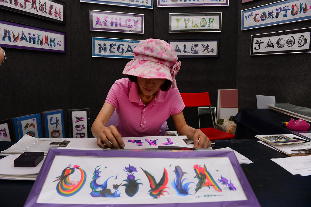 . Korean calligraphy artist Diane Yoon uses a leather brush and water color paints to create her unique Rainbow Art calligraphy during the Taste of Colorado festivities at Civic Center Park in Denver on August 31, 2014.  The paintings, each unique, sell for only $2.00 a letter and were hugely popular at the festival. (Photo By Helen H. Richardson/ The Denver Post)