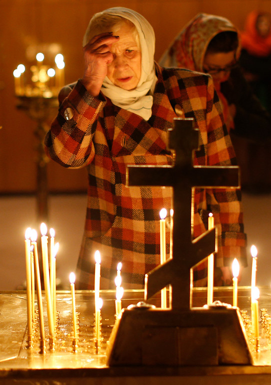 . Lithuanian Orthodox believers light candles during an Easter vigil mass in the Prechistensky, the Cathedral Palace, in Vilnius, Lithuania, Saturday, April 19, 2014. (AP Photo/Mindaugas Kulbis)