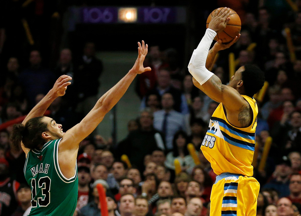 . Denver Nuggets\' Andre Iguodala (R)  puts up the game-winning basket over Chicago Bulls\' Joakim Noah during the overtime of their NBA basketball game in Chicago, Illinois, March 18, 2013.   REUTERS/Jim Young