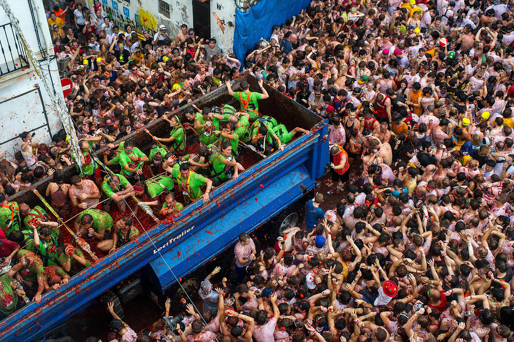 . Revelers throw tomatoes while participating the annual Tomatina festival on August 28, 2013 in Bunol, Spain. An estimated 20,000 people threw 130 tons of ripe tomatoes in the world\'s biggest tomato fight held annually in this Spanish Mediterranean town.  (Photo by David Ramos/Getty Images)