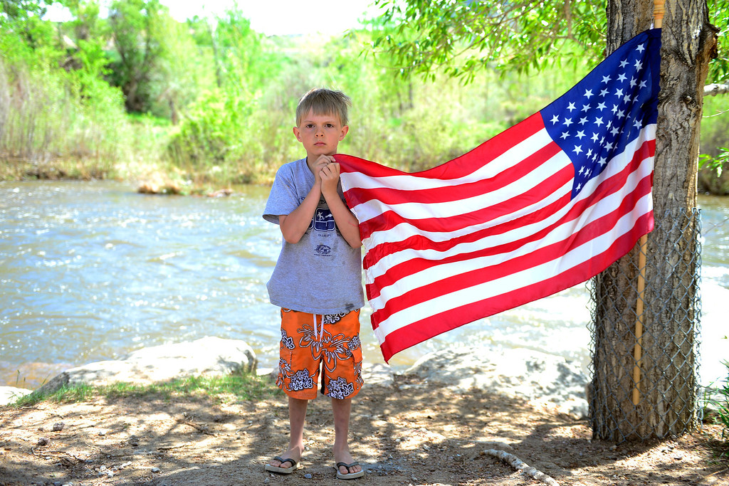 . Collin Mullen, 6, holds an American flag near the water during Golden Games at the Clear Creek Whitewater Park. (Photo by AAron Ontiveroz/The Denver Post)