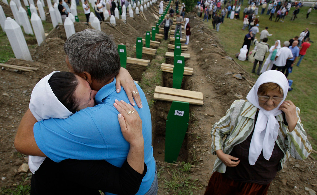 . A Bosnian woman is comforted by family members during a funeral ceremony at the memorial center in Potocari, near Srebrenica, 160 kms east of Sarajevo, Bosnia, Thursday, July 11, 2013. People from around Bosnia and abroad have begun arriving in Srebrenica Thursday to commemorate 18th anniversary of the 1995 massacre and rebury recently identified victims exhumed from mass graves. The victims\' bodies are still being exhumed from mass graves in the area, where Serbs had dumped them in an attempt to cover up the crime. Identified victims are buried each year on the massacre\'s anniversary at a memorial cemetery near Srebrenica. (AP Photo/Amel Emric)