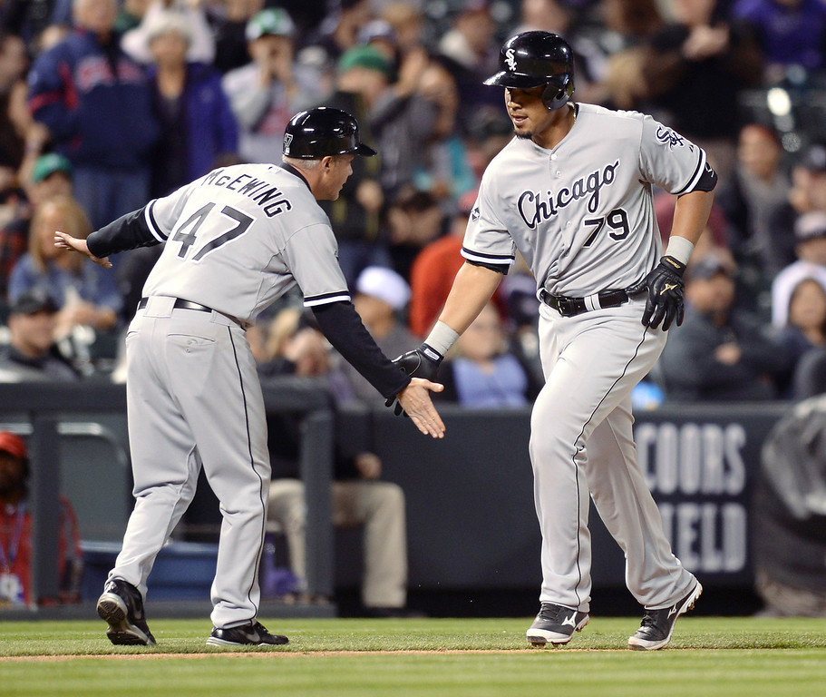. Chicago coach Joe McEwing congratulated Jose Abreu following his three-run home run off Colorado reliever Chad Bettis in the seventh inning  (Photo by Karl Gehring/The Denver Post)