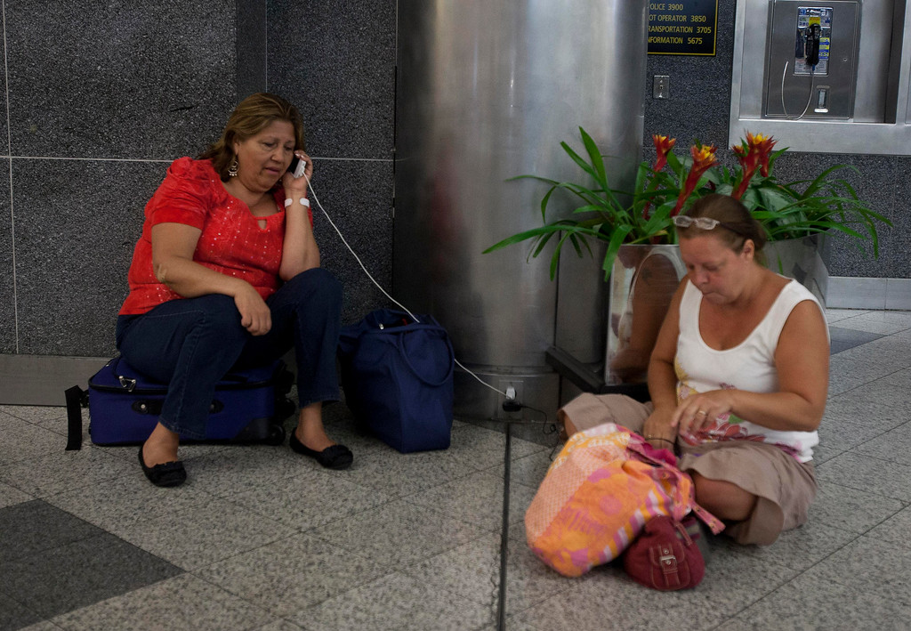 . Stranded passengers, who had their flights cancelled when a Southwest Airlines 737 made an emergency landing, sit on the floor at LaGuardia airport in New York, July 22, 2013. Eight people were injured on Monday when the landing gear on a Southwest Airlines  jet collapsed upon touchdown at New York City\'s LaGuardia Airport, officials said.    REUTERS/Carlo Allegri
