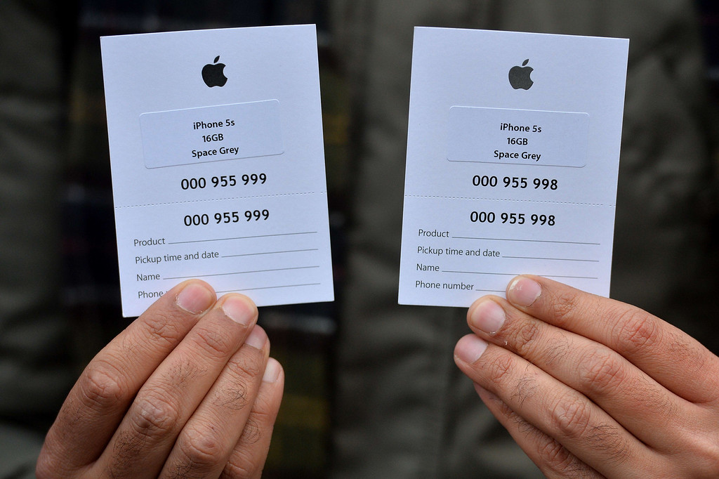 . A customer holds two vouchers as he queues outside the Apple store ahead of the iPhone 5S and 5C going on sale in central London on September 20, 2013.   Apple\'s eagerly-awaited iPhone 5S and 5C went of sale in London at 8am. AFP PHOTO / BEN STANSALL/AFP/Getty Images