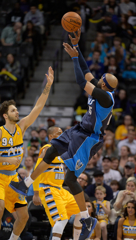 . Dallas Mavericks shooting guard Vince Carter (25) takes an off balance shot over Denver Nuggets shooting guard Evan Fournier (94) during the first quarter March 5, 2014 at Pepsi Center. (Photo by John Leyba/The Denver Post)