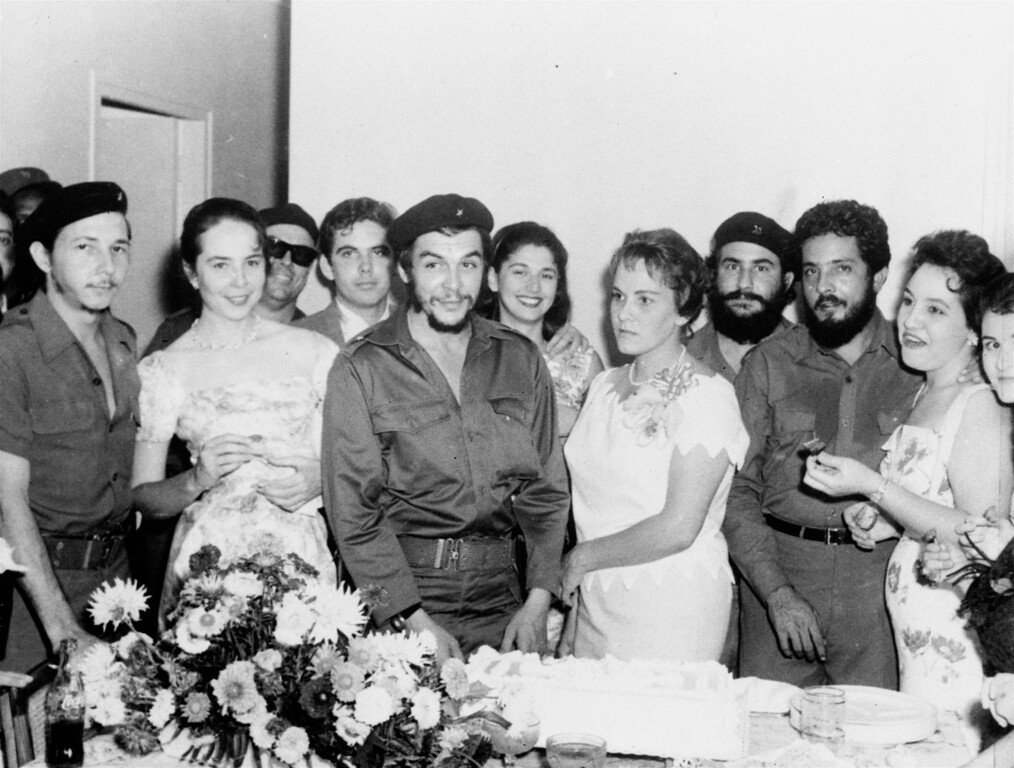 """. Major Ernesto \""""Che\"""" Guevara, 34, Argentine hero of the Cuban revolution, and his bride Aleida, stand before the wedding cake following their marriage at a civil ceremony at La Cabana Military fortress, March 23, 1959.  At the extreme left is Maj. Raul Castro, commander in chief of the armed forces and brother of Prime Minister Fidel Castro.  Next to Major Castro stands his wife, Vilma Esping. (AP Photo)"""