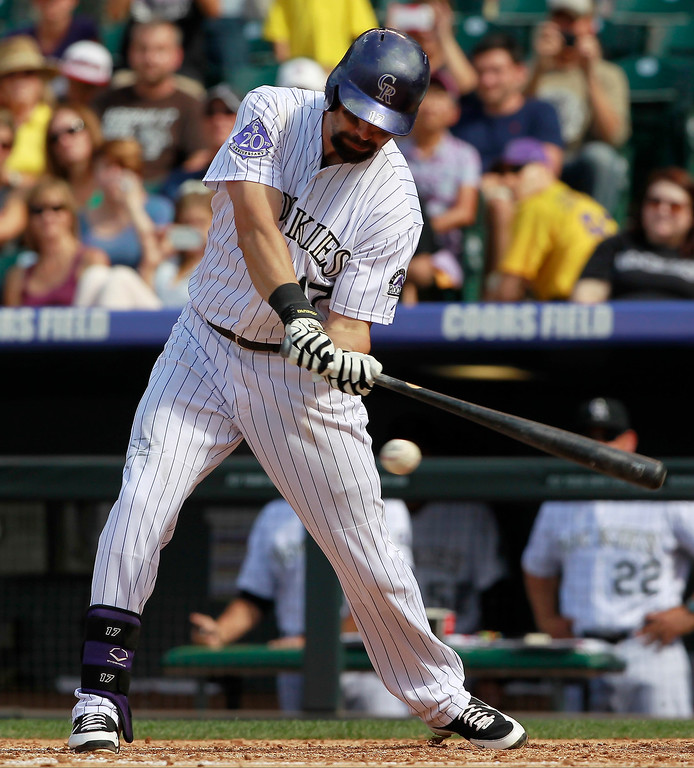 . Colorado Rockies\' Todd Helton strikes out while swinging at pitch against the Cincinnati Reds in the fourth inning of a baseball game in Denver, Sunday, Sept. 1, 2013. (AP Photo/David Zalubowski)