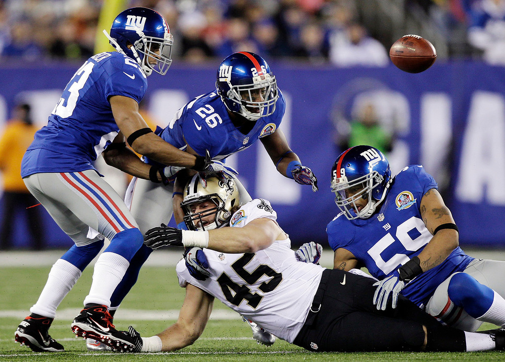 . New Orleans Saints fullback Jed Collins (45) fumbles as New York Giants cornerback Corey Webster (23), Antrel Rolle (26) and Michael Boley (59) try to recover the ball during the first half of an NFL football game, Sunday, Dec. 9, 2012, in East Rutherford, N.J. (AP Photo/Kathy Willens)