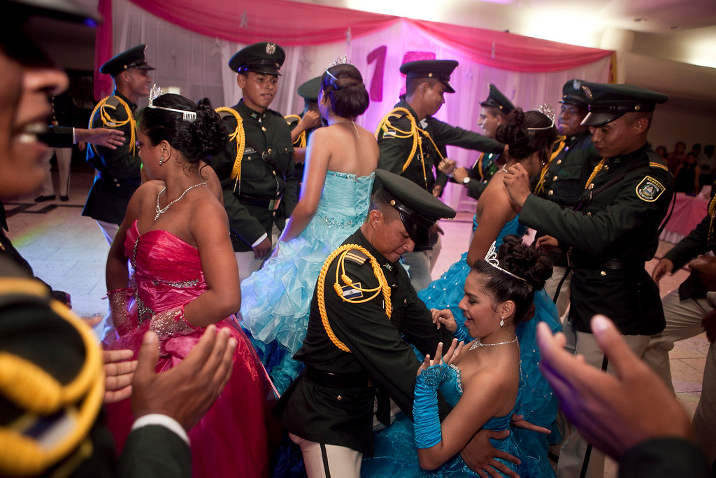 ". In this Saturday, Sept. 21, 2013, Nicaraguan girls dance with army cadets during a ""quinceanera\"" party in Managua, Nicaragua. Nicaraguaís Association of Mothers and Fathers of Children with Cancer and Leukemia put on for the fifith year, a the traditional coming out party for the girls from poor, rural families, teens who have the added burden of dealing with cancer. This yearís party feted 37 girls between ages 14 and 16. (AP Photo/Esteban Felix)"