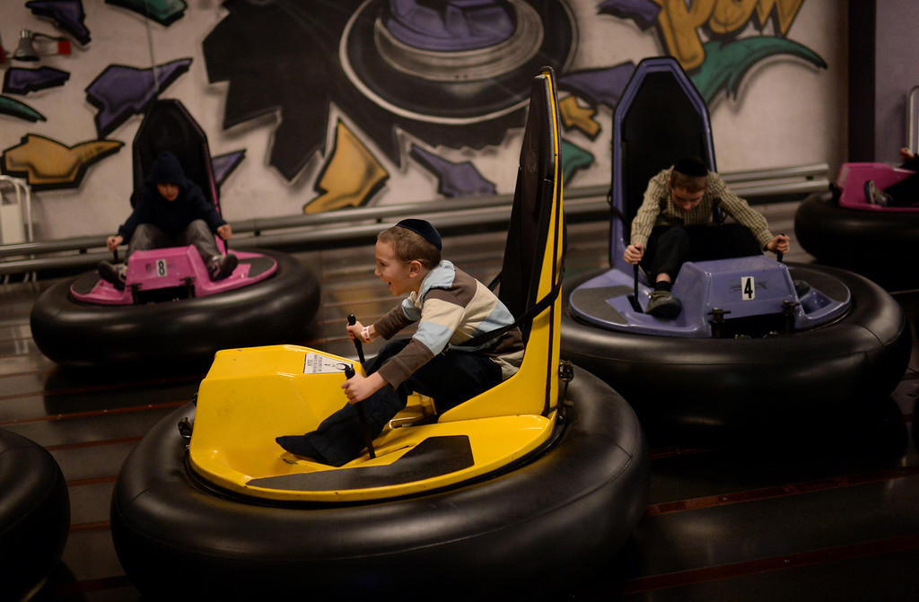 . CENTENNIAL, CO. DECEMBER 25: Moshe Krausz, 6, front, and his friends ride the bumper cars at the the South Suburban Sports Center in Centennial, Colorado December 25, 2013. For the fourteenth year, the Denver Community Kollel Women\'s Division is offering a Jewish Family Extravaganza of family fun and entertainment. (Photo by Hyoung Chang/The Denver Post)