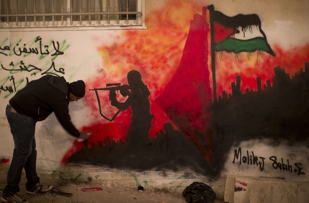 . A Palestinian man sprays a mural on a wall near the family home of Palestinian prisoner Ahmad Shehadah in the Qalandia refugee camp near the city of Jerusalem on December 30, 2013 as they prepare for his imminent release from Israeli prison alongside 26 other Palestinians. The 26 prisoners expected to be released late in the evening were jailed before the signing of the 1993 Oslo accords, which formally launched the Middle East peace process, and have served 19 to 28 years for killing Israeli civilians or soldiers.  AHMAD GHARABLI/AFP/Getty Images
