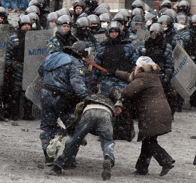 . A woman hits a riot police officers with a cross as he pulls a protester during clashes in the center of Kiev on January 22, 2014. AFP PHOTO / ANATOLIY STEPANOV/AFP/Getty Images