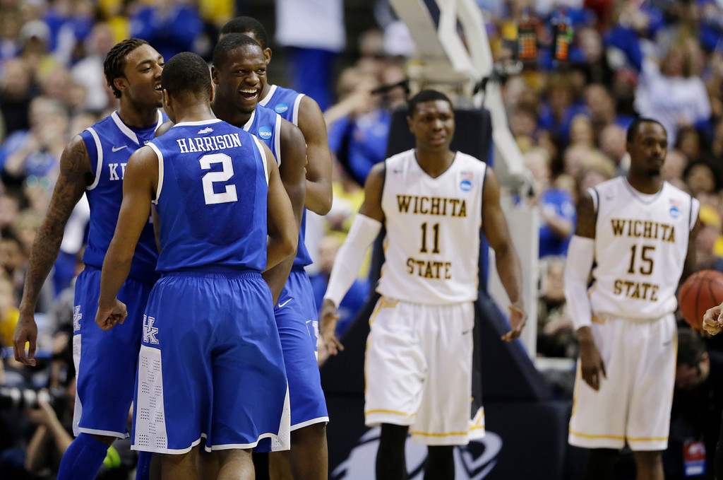 . Kentucky players from left, guard/forward James Young (1), guard Aaron Harrison (2) and forward Julius Randle (30) celebrate against Wichita State during the second half of a third-round game of the NCAA college basketball tournament Sunday, March 23, 2014, in St. Louis. (AP Photo/Jeff Roberson)