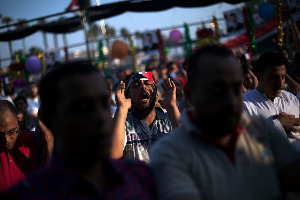 ". Supporters of Egypt\'s ousted President Mohammed Morsi pray during the celebration of the ""Eid al-Fitr\"" holiday (end of Ramadan) near Cairo University in Giza, Egypt, Thursday, Aug. 8, 2013. This year\'s holiday is overshadowed by the deep divisions in Egypt, with the interim government planning to celebrate the feast with outdoor prayers and protests in town center squares and Morsi\'s supporters marking the holiday with their own protests and prayers, including at the two major sit-ins by the Islamists in Cairo. (AP Photo/Manu Brabo)"