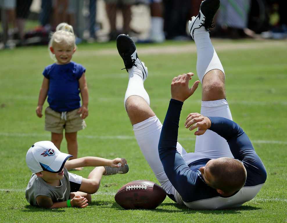 . Tennessee Titans punter Brett Kern plays with his son, Bryce, 4, and daughter, Anelle, 2, after practice at NFL football training camp Monday, July 28, 2014, in Nashville, Tenn. (AP Photo/Mark Humphrey)