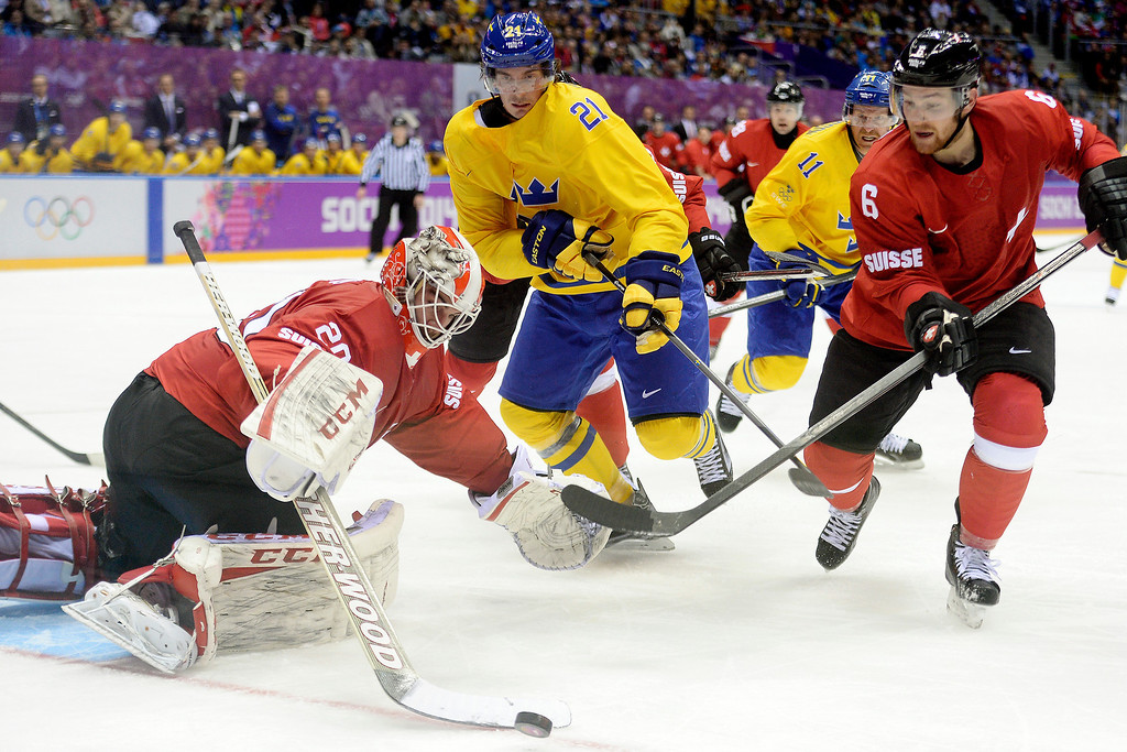 . SOCHI, RUSSIA - FEBRUARY 14: Switzerland goalie Reto Berra defends a shot by Sweden\'s Loui Eriksson as teammate Yannick Weber defends during the action at Bolshoy Arena. Sochi 2014 Winter Olympics on Friday, February 14, 2014. (Photo by AAron Ontiveroz/The Denver Post)