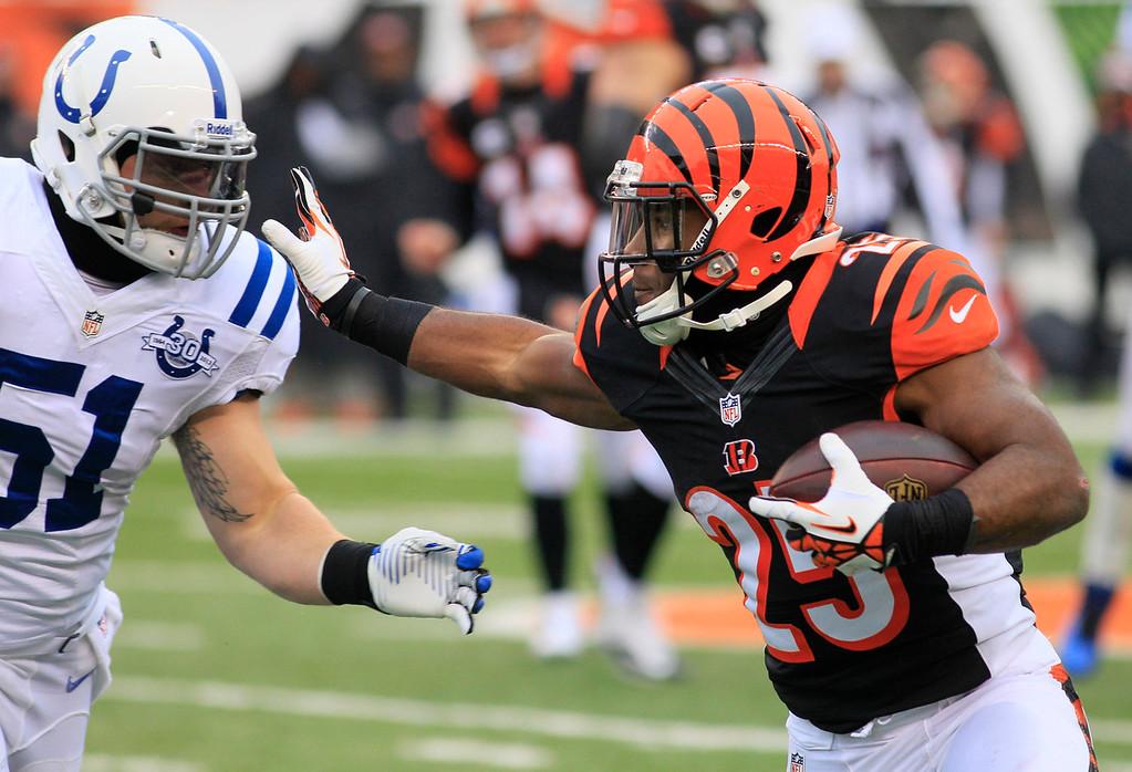 . Cincinnati Bengals running back Gio Bernard (25) runs against Indianapolis Colts inside linebacker Pat Angerer (51) in the second half of an NFL football game, Sunday, Dec. 8, 2013, in Cincinnati. (AP Photo/Tom Uhlman)